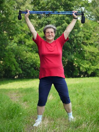 Senior woman doing a series of warm-up exercises with walking poles