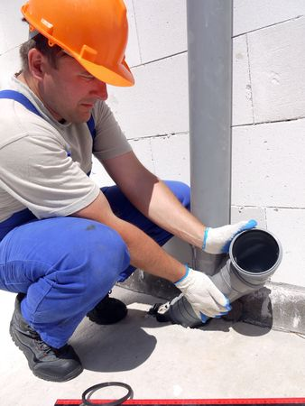 riool: Loodgieter montage pvc rioleringsbuizen binnen nieuw gebouwde huis Stockfoto