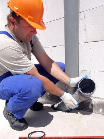 Plumber assembling pvc sewage pipes inside newly built house