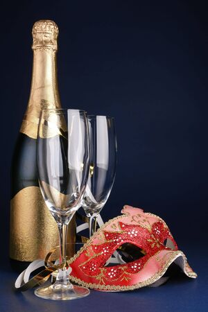 Venetian mask, bottle of champagne and two glasses over dark blue background photo