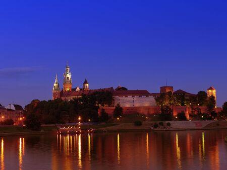 wawel: Royal Wawel Castle illuminated at night reflecting in the Vistula river, Krakow - Poland Stock Photo