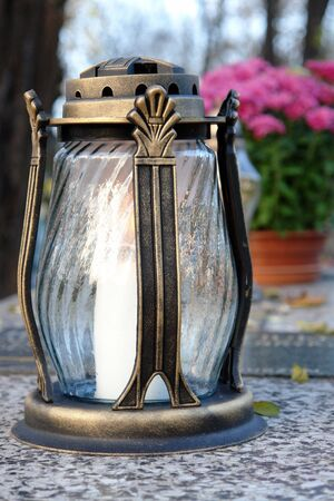 votive candle: Glass votive candle lit on marble tombstone Stock Photo