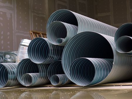 Pile of steel corrugated pipes stacked at construction site Standard-Bild