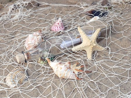 Starfish, seashells and bottle with message caught in the fishing net photo