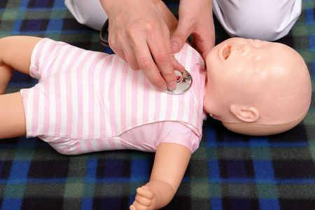 cpr: First aid instructor using infant dummy to demonstrate how to examine baby with stethoscope