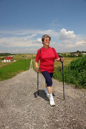 Senior woman doing nordic walking in the countryside Standard-Bild