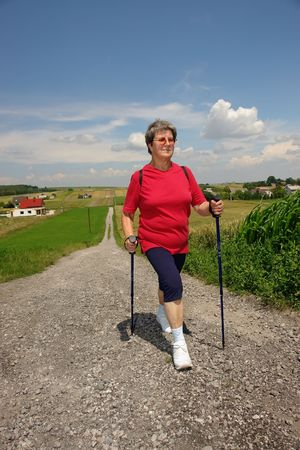 nordic country: Senior woman doing nordic walking in the countryside Stock Photo
