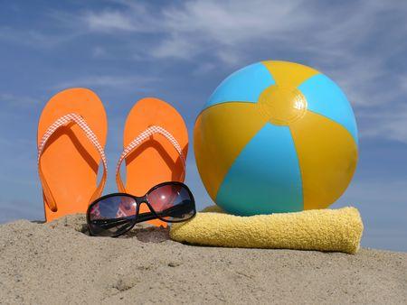 sandalia: Naranja chancletas impulsado verticalmente en la arena de la playa, gafas de sol, playa, bal�n inflado y amarillo toalla de ba�o sobre cielo azul Foto de archivo