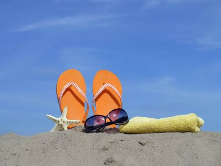 Orange flip-flops driven vertically into beach sand, starfish, sunglasses and yellow bath towel over blue sky Stock Photo