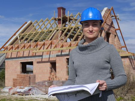 Female architect wearing blue helmet posing with building plans against unfinished brick house Stock Photo