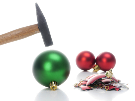 destroy: Hammer hitting christmas ball breaking it into pieces - concept depicting aversion to celebrate christmas holidays