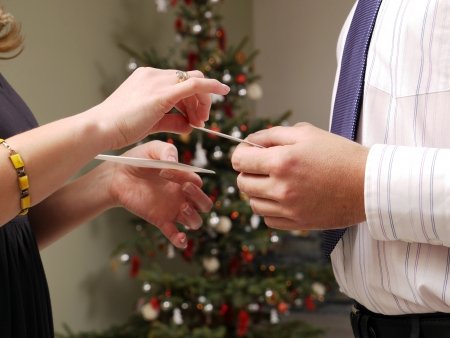 Closeup of young couple hands sharing traditional Christmas Eve wafer with Christmas tree in the background