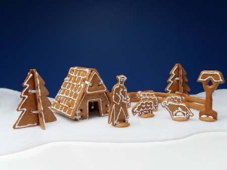 Winter scene arranged from gingerbread figures representing shepherd with flock of sheep and hut photo