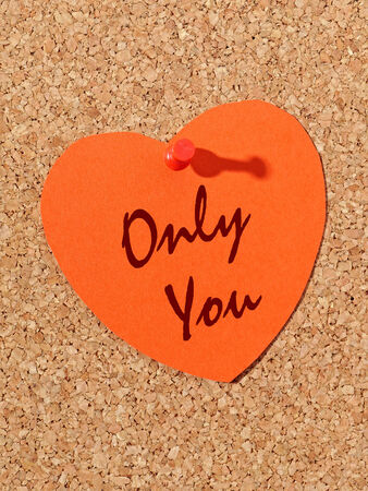 Red paper heart with Only You text pinned to the corkboard photo