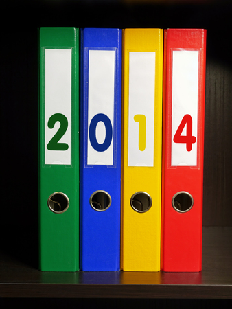 Four color binders with New Year 2014 digits placed on bookshelf photo