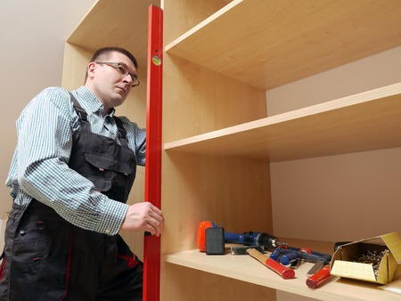 Carpenter using spirit level for leveling assembled wardrobe furniture