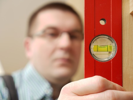 Closeup shot of carpenter looking at spirit level gauge to check verical positioning of furniture - shallow depth of field Stock Photo