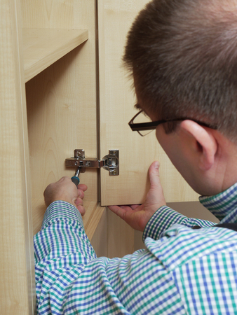 Carpenter fitting wardrobe hinge doors in walk-in closet Stock Photo - 25114719