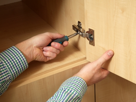 adjusting screw: Carpenter fitting wardrobe hinge doors in walk-in closet