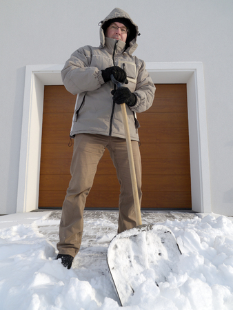 snowbank: Man clearing driveway of snow with shovel after heavy snowing