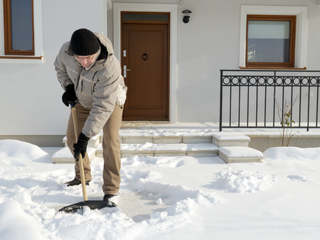 Man clearing path to his house of snow with shovel after heavy snowing photo