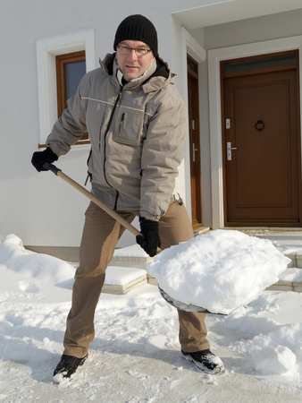 snow clearing: Man clearing path to his house of snow with shovel after heavy snowing Stock Photo