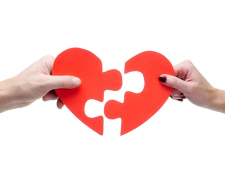 Male and female hand matching red jigsaw heart halves over white background photo