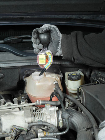 Auto mechanic performing antifreeze coolant freeze-up protection test using a tester Stock Photo