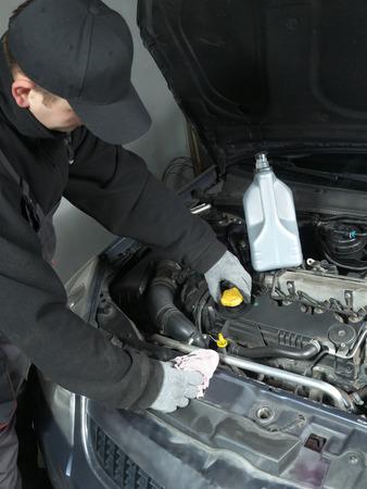 replenishing: Auto mechanic unscrewing oil filler cap Stock Photo