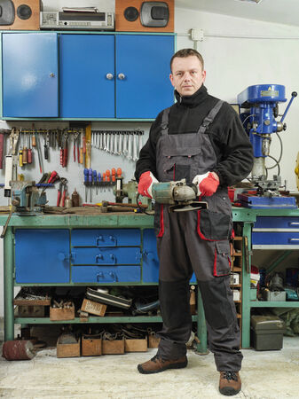 angular: Locksmith holding angular grinder while posing in his workshop Stock Photo