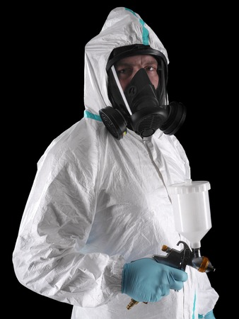 Spray painter wearing white coverall, respirator and spray gun shot over black background photo