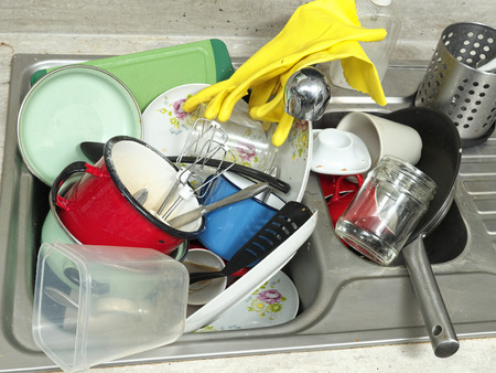 Kitchen sink full of dirty kitchenware photo