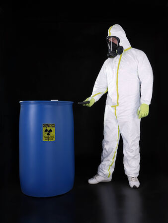 safety signs: Man wearing protective suit checking radioactivity level of radioactive substance stored in blue container