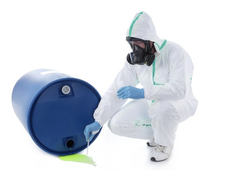 Man wearing protective suit and respirator sampling dangerous chemical liquid leaking from blue container Stock Photo