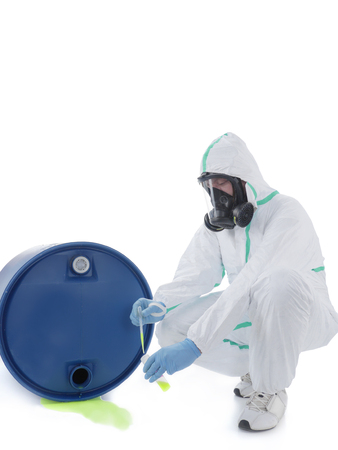 respirator: Man wearing protective suit and respirator sampling dangerous chemical liquid leaking from blue container Stock Photo