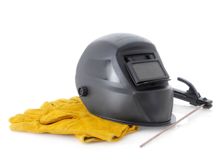electrode: Black welding hood,welding electrode holder and yellow protective leather gloves over white
