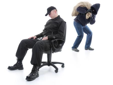 sleeping bag: Security man sleeping on armchair being unaware of masked burglar stealing behind his back