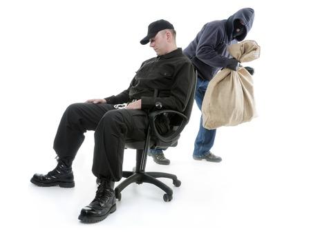 a watchman: Security man sleeping on armchair being unaware of masked burglar stealing behind his back