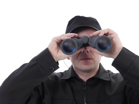Security man wearing black uniform looking through binocular, shot on white Фото со стока - 25987937