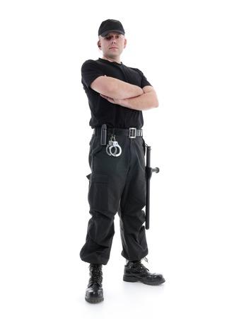 Sécurité homme portant l'uniforme noir équipé avec le club de la police et des menottes debout en toute confiance avec les bras croisés, coup sur blanc Banque d'images - 25987945