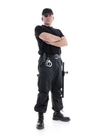 Security man wearing black uniform equipped with police club and handcuffs standing confidently with arms crossed, shot on white Standard-Bild