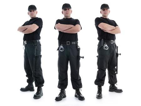 guardia de seguridad: Tres agentes de seguridad vestidos de uniforme negro equipado con porras y esposas se coloca con confianza con los brazos cruzados de izquierda a derecha, a tiros en blanco Foto de archivo