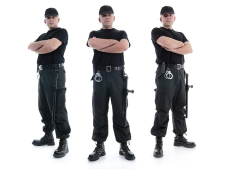 Three security men wearing black uniform equipped with police clubs and handcuffs standing confidently with arms crossed from left to right, shot on white Banque d'images