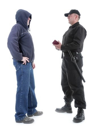 warden: Policeman in black uniform checking ID of hooded suspect, shot on white Stock Photo