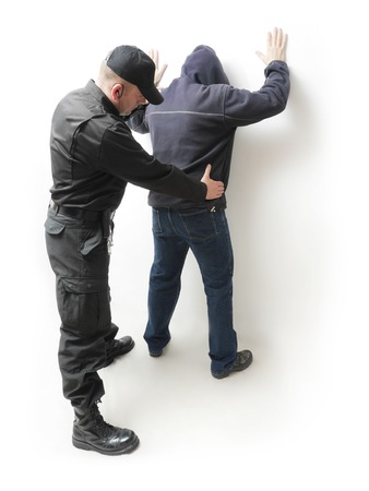 arrested criminal: Man being searched by a policeman in black uniform Stock Photo