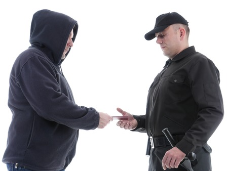 carding: Policeman in black uniform checking ID of hooded suspect, shot on white Stock Photo