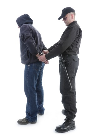 Policeman handcuffing hooded man, shot on white Banque d'images