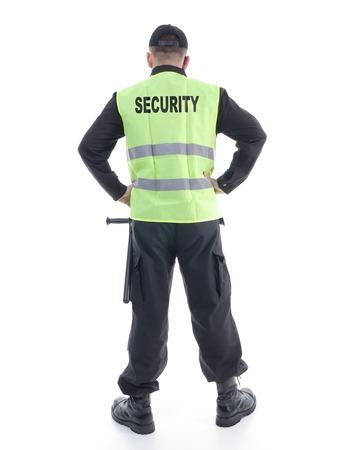 ホワイト ショット セキュリティ男は、両手を腰に休んで自信を持って立っている黒の制服と黄色の反射ベストを着て、カメラに直面しています。