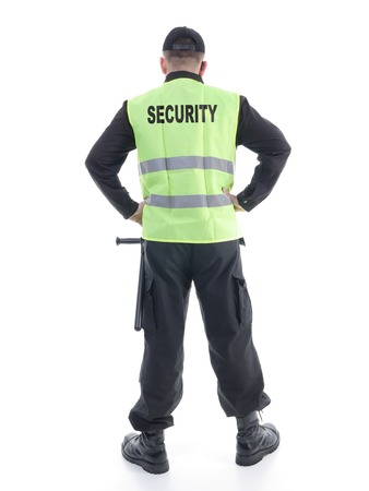 Security man wearing black uniform and yellow reflective vest standing confidently with arms resting on hips, facing back to the camera, shot on white photo