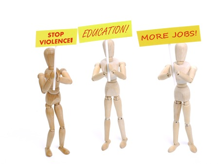 Three wooden dummy demonstrators holding placards saying - Stop Violence, Education and More Jobs shot on white background